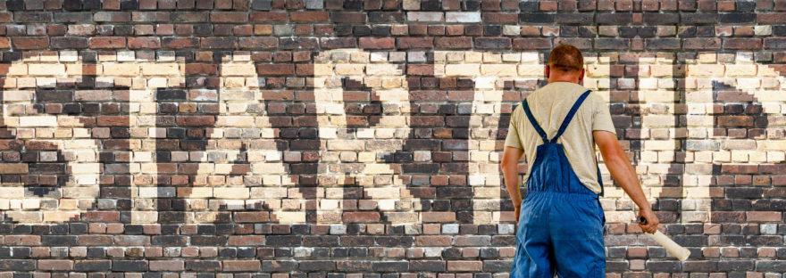 Painter paints Startup on brick wall